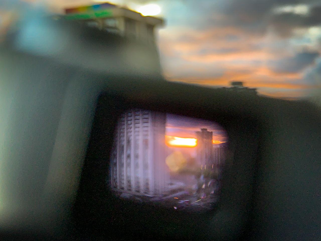 ILLUMINATED CAR AGAINST SKY DURING SUNSET SEEN THROUGH WINDOW