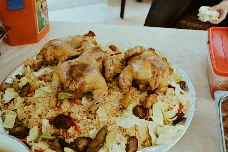 A Taste Of Life homemade Biryani with three whole chickens on top.