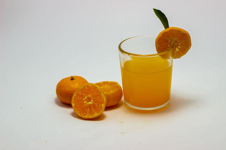 Orange fruit on table against white background