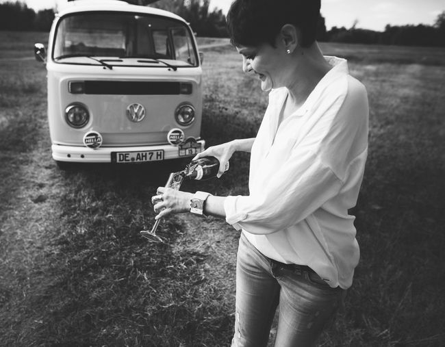 Side view of a woman holding camera on field