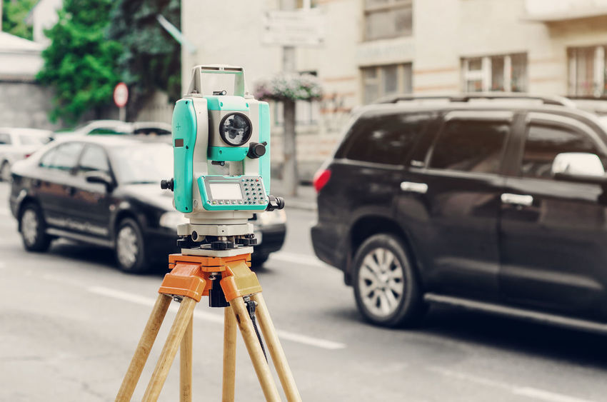 Surveyor device electronic total station on the street. Measurement of the relief. Architecture Building Exterior Built Structure Car City City Life Communication Day Focus On Foreground Land Vehicle Mode Of Transportation Motor Vehicle No People Outdoors Road Sign Stationary Street Tachymeter Technology Transportation