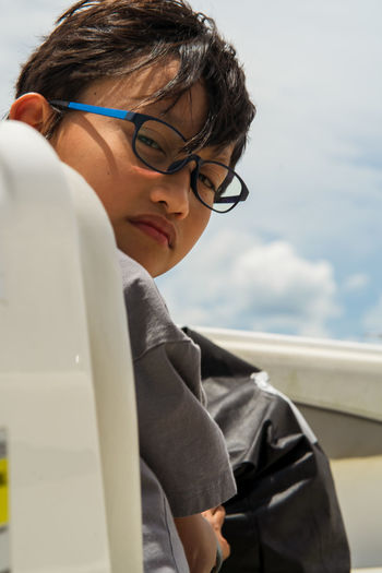 Portrait of boy with eyeglasses against sky