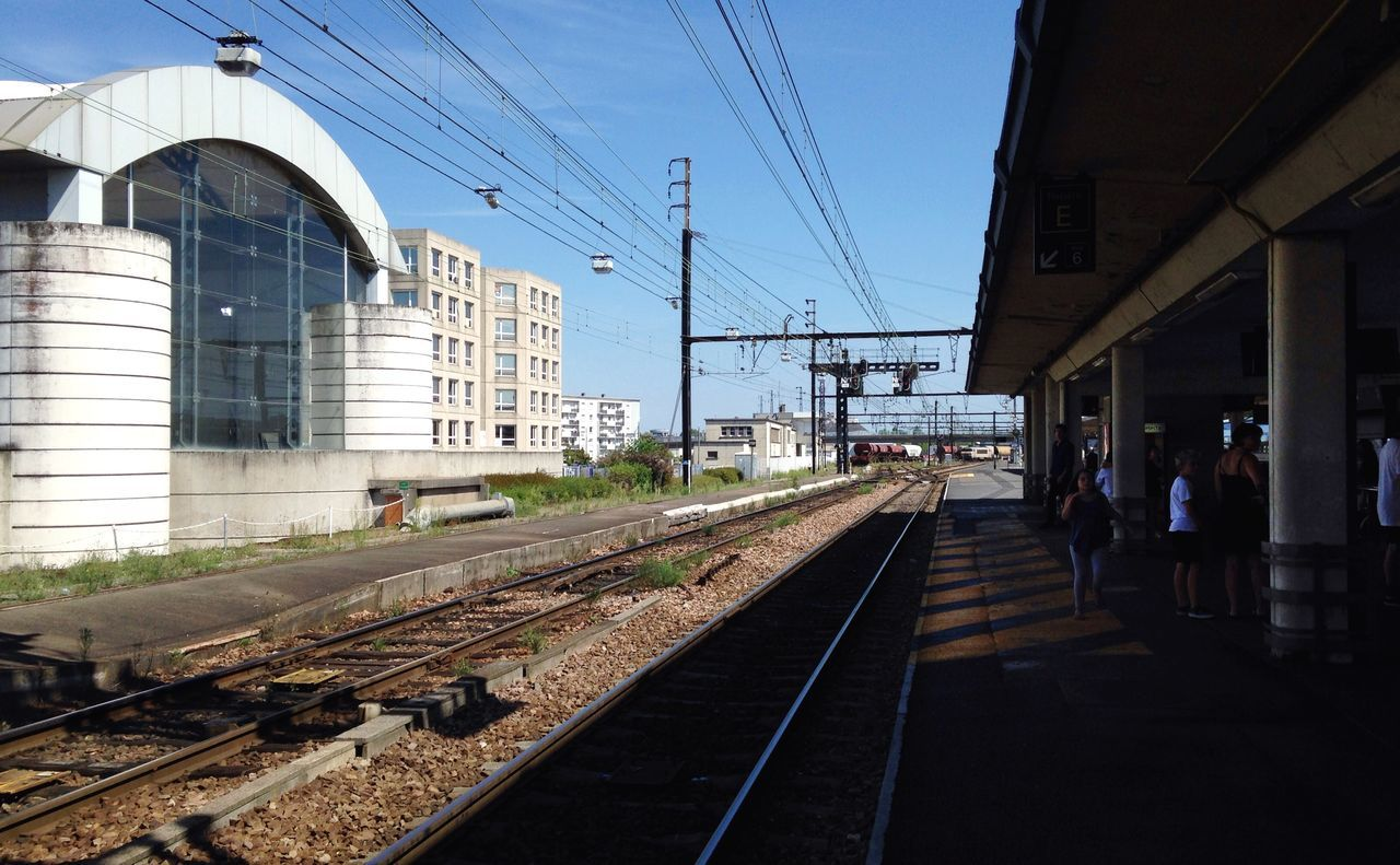 Railroad Station By Building Against Clear Blue Sky