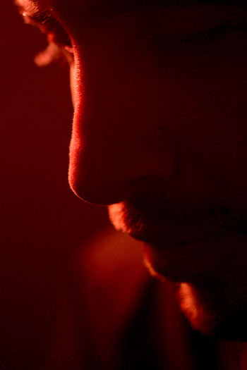 Close-Up Of Depressed Man In Red Lit Room