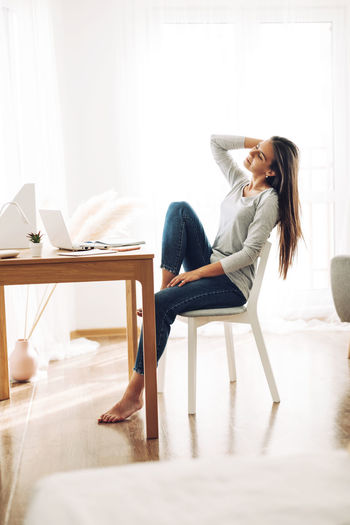 A beautiful girl is sitting leaning back in a chair and stretching after work at a laptop