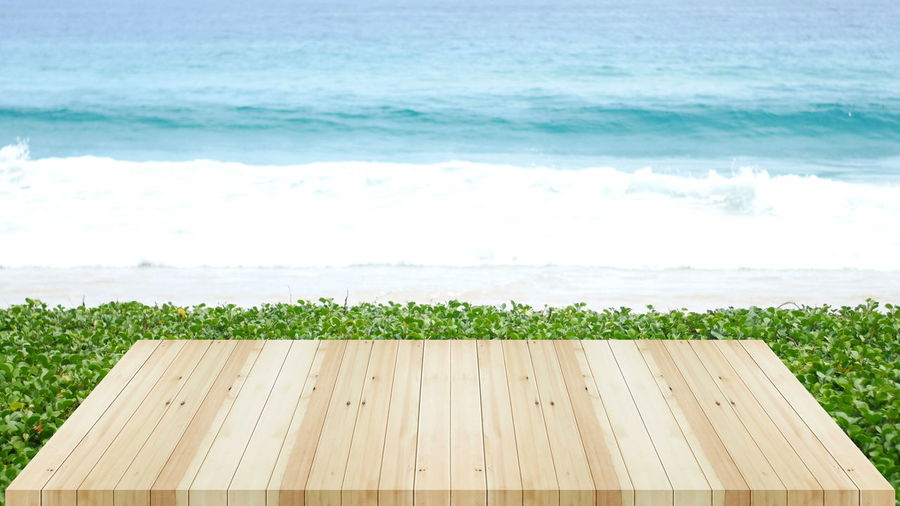 Wood table on beach sea in the summer. Water Sea Wood - Material Nature Land Beach No People Green Color Beauty In Nature Day Plant Horizon Outdoors Sky Growth Tranquility Sport Horizon Over Water Grass