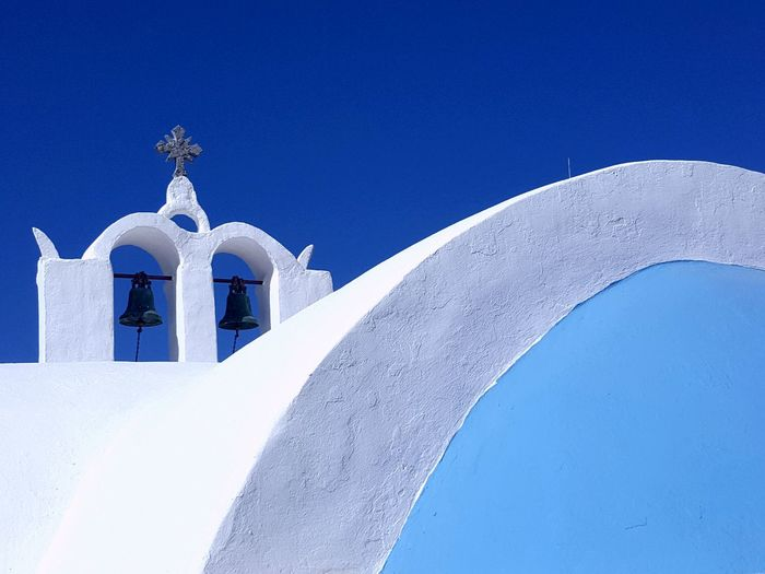 Low angle view of bells on whitewashed church against clear blue sky