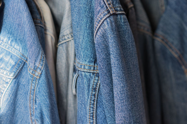 denim Adult Blue Casual Clothing Choice Close-up Clothing Denim Fashion Garment Hanging Human Body Part Indoors  Jacket Jeans Midsection People Retail  Textile Variation
