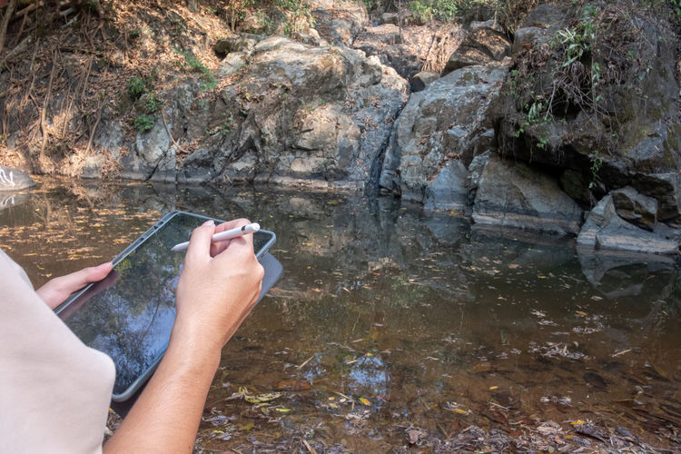 Midsection of person holding rock in water
