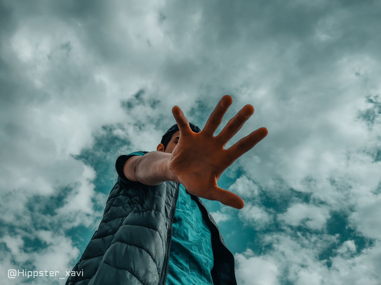 LOW ANGLE VIEW OF HUMAN HAND AGAINST CLOUDY SKY