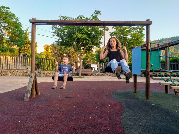 Full length of mother and son swinging in playground