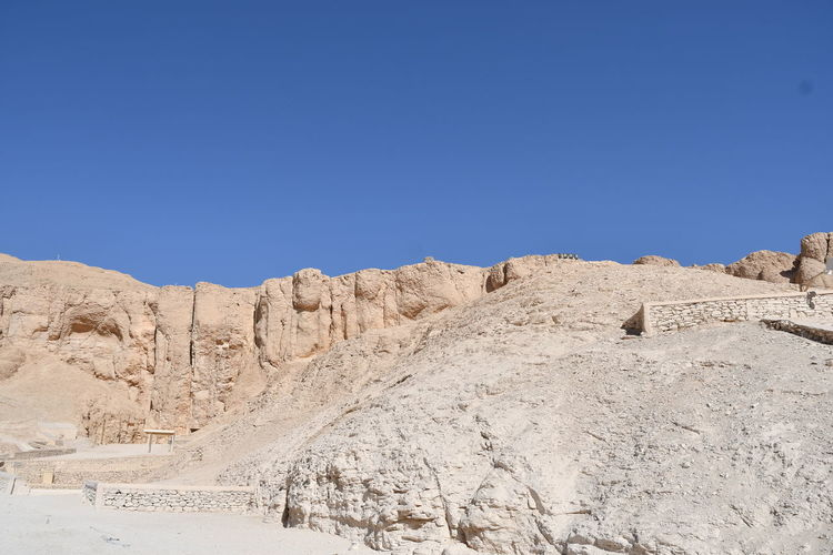 Panoramic view of arid landscape against clear blue sky