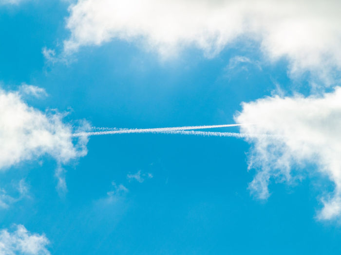 Low Angle View Of Vapor Trail And Clouds In Blue Sky