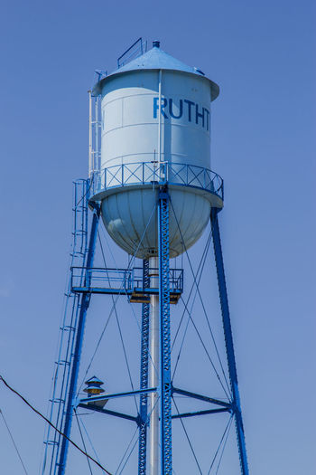 Low angle view of water tower against clear blue sky