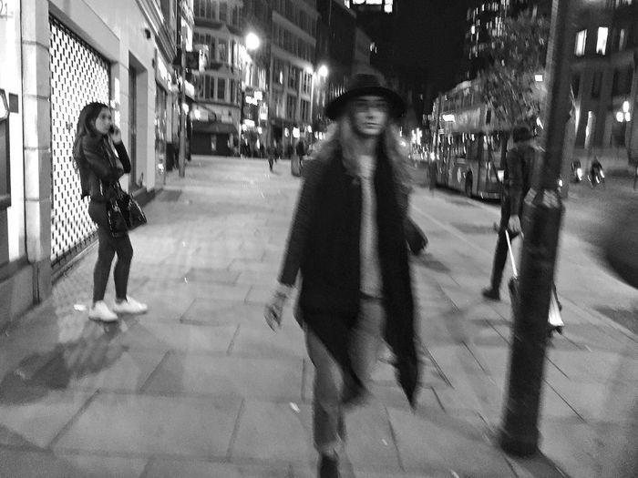 Woman standing on illuminated city street at night
