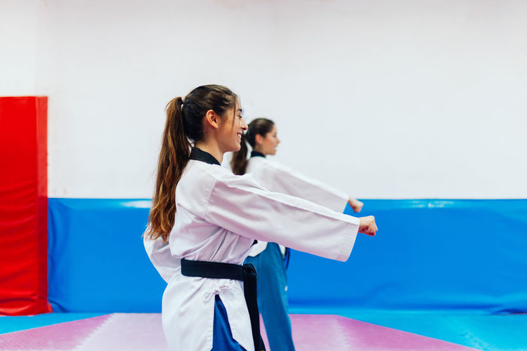 Side view of women practicing karate at gym