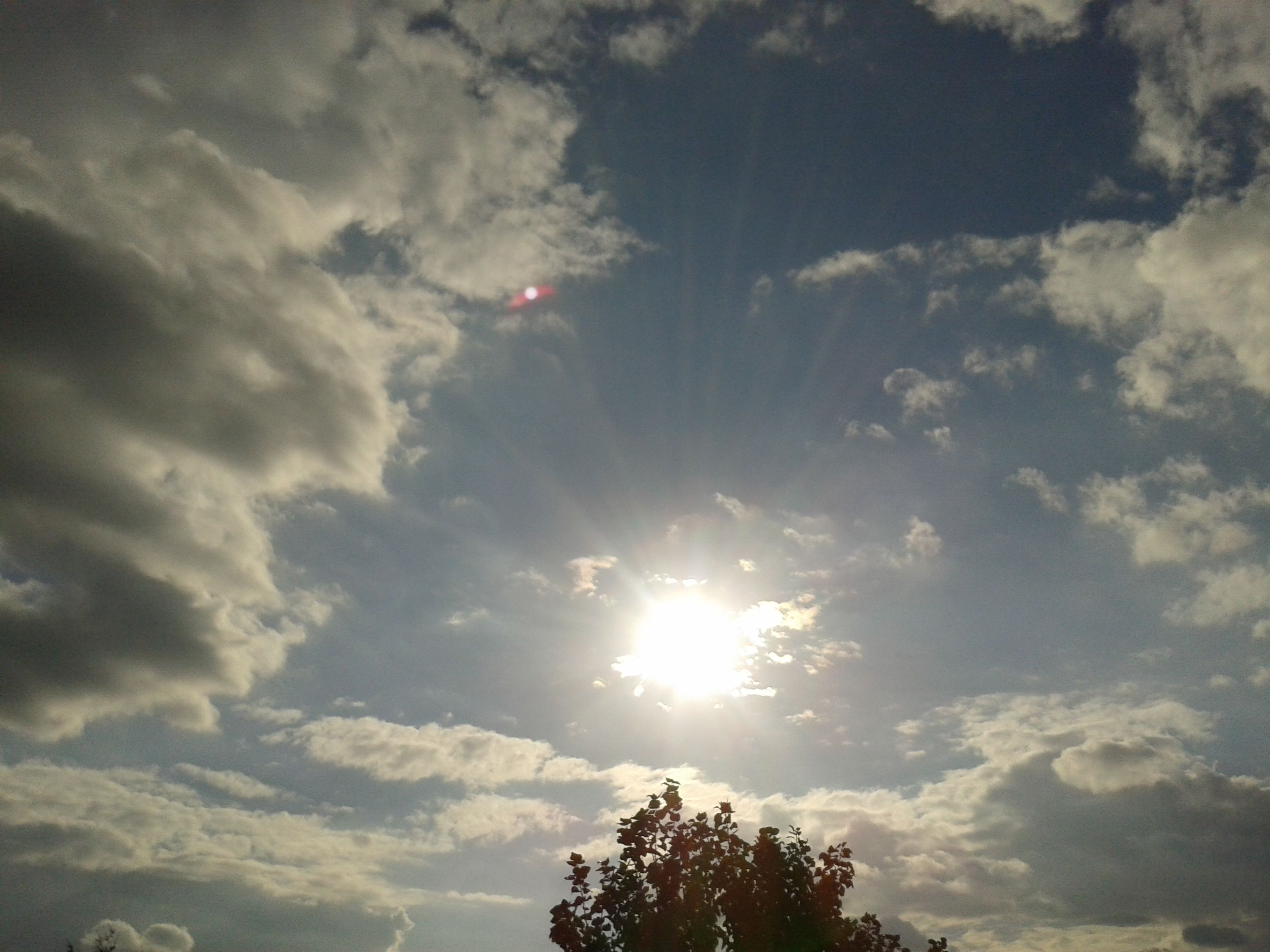 low angle view, sun, sky, tree, sunbeam, cloud - sky, sunlight, beauty in nature, tranquility, lens flare, silhouette, nature, scenics, tranquil scene, bright, cloud, cloudy, outdoors, idyllic, no people