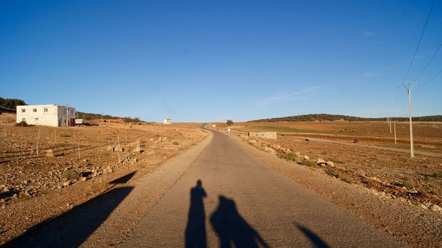 Shadow of man on road against clear sky