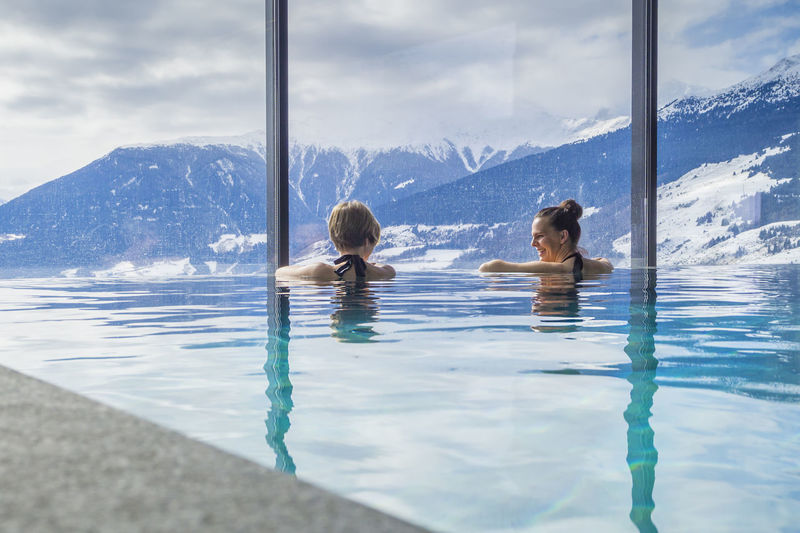 Rear view of female friends swimming in pool against snowcapped mountains