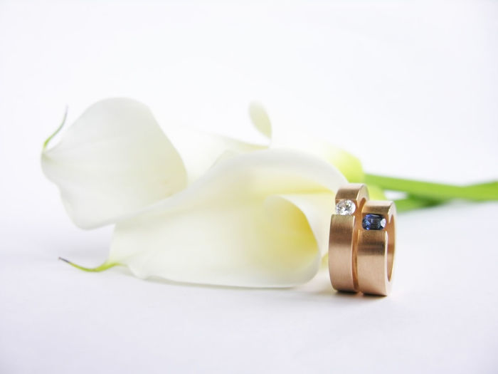 Wedding rings and calla flower Calla Close-up Color Compromise Copy Space Diamond Diamond Ring Engagement Ring Flower Gemstone  Gold Indoors  Love Luxury No People Precious Gemstone Ring Romantic Saphire Studio Shot Wedding Wedding Rings White Background