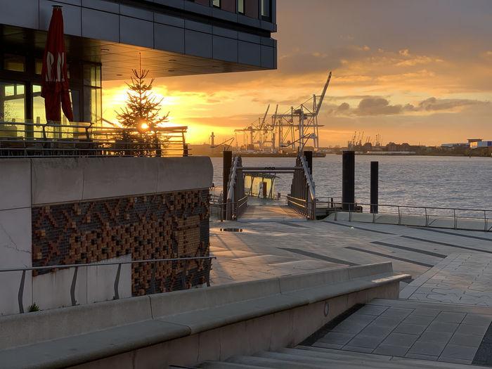 Footpath by sea against orange sky