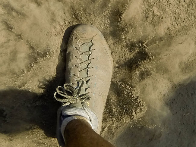Close-up Communication Day Dust Dust Cloud Foot High Angle View Human Body Part Low Section One Person Outdoors People Real People Sand Sea Shoe Tanzania Text Water