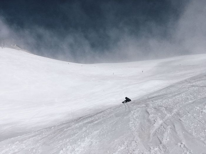 Low angle view of person on snowcapped mountain against sky