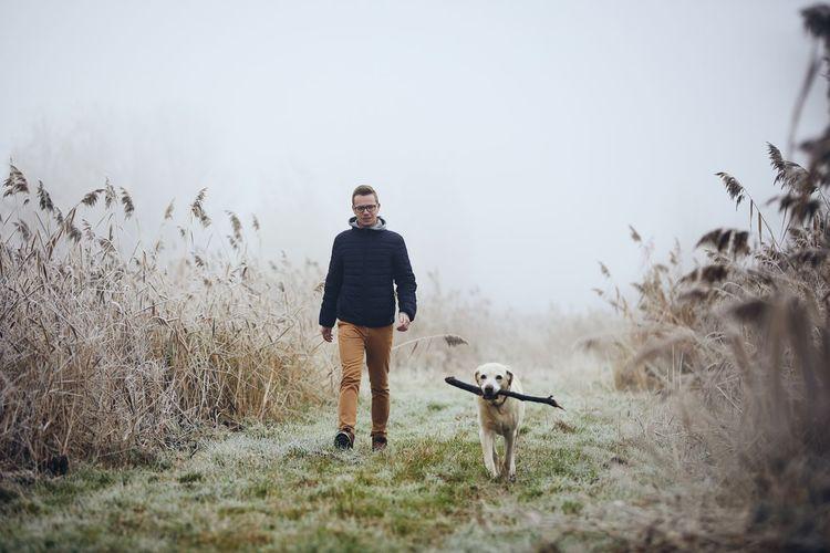 Full length of man with dog walking on land