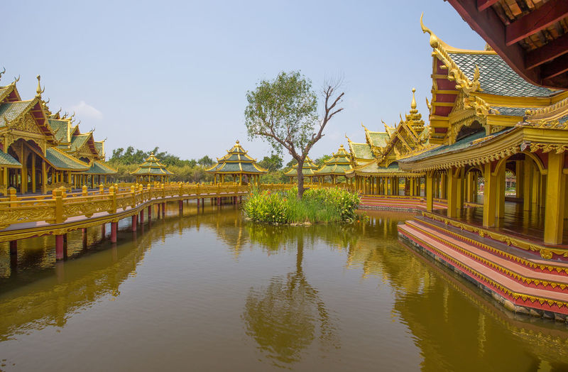 Panoramic view of temple by lake and buildings against sky