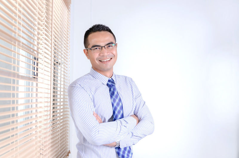 Portrait Of Smiling Businessman With Arms Crossed Standing At Office