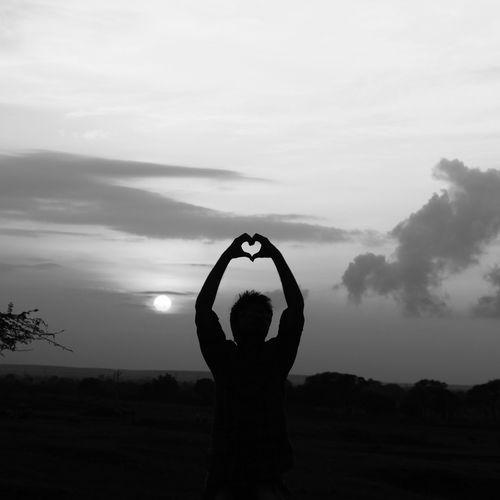 Silhouette man showing heart shaped on field