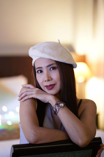 Portrait of woman wearing hat while sitting at home