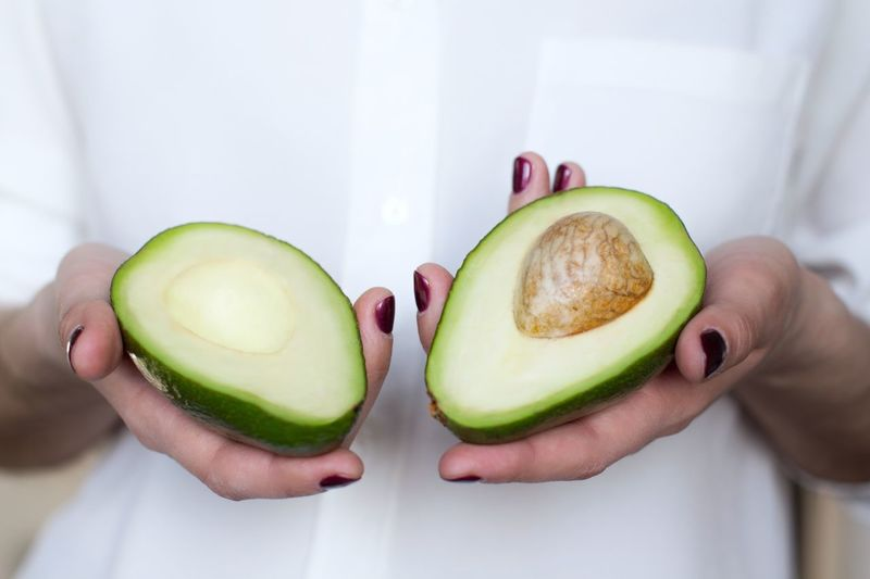Woman holding two halves of an avocado Nutrition Snack Time! Breakfast Dieting Vitamin Organic Raw Food Vegan Vegetarian Food Preparation  Avocado Food And Drink Healthy Eating Wellbeing Human Hand Holding Lifestyles Freshness