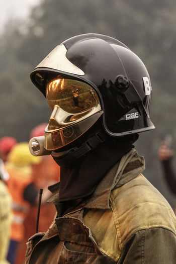 Close-Up Of Firefighter Wearing Crash Helmet While Standing Outdoors
