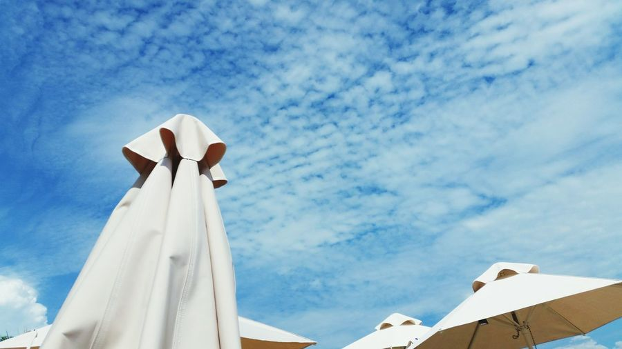 Low angle view of white umbrella against blue sky