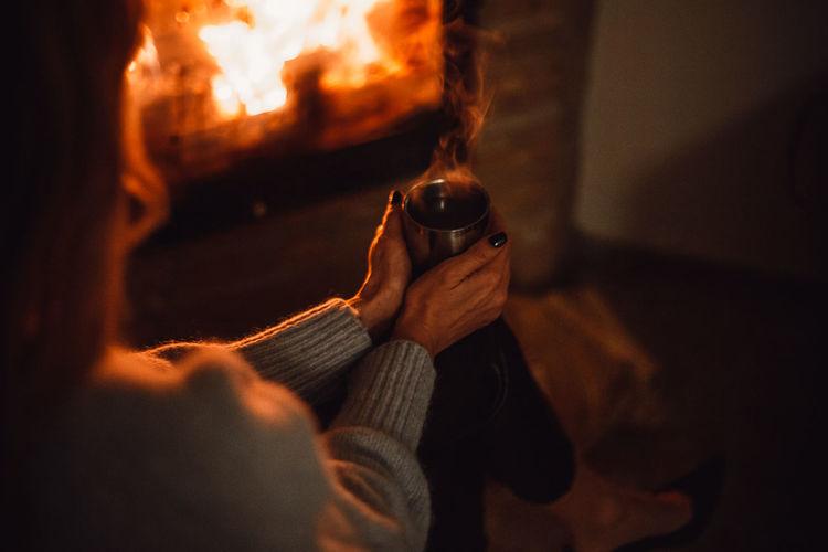 Close-up of man holding burning candle
