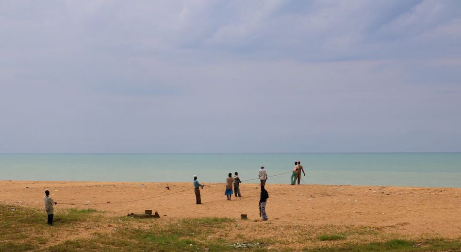 People pulling rope on beach against sky