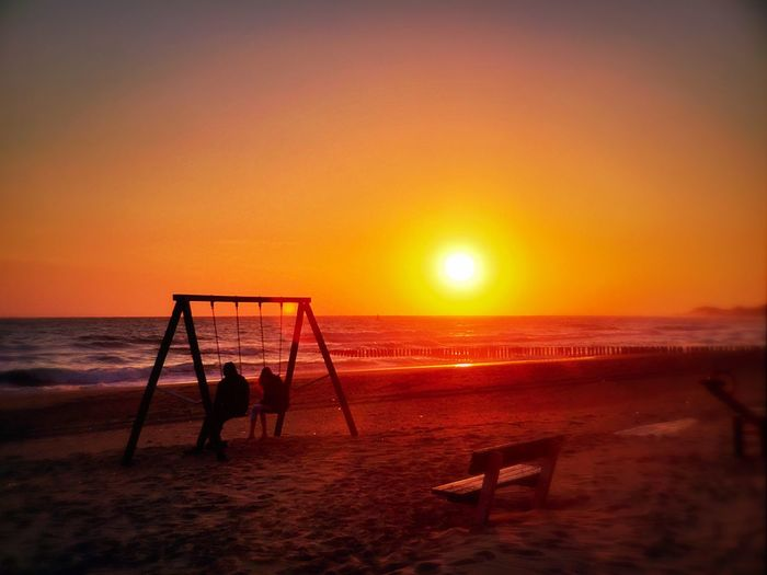 Silhouette People Sitting On Swings At Beach Against Orange Sunset Sky