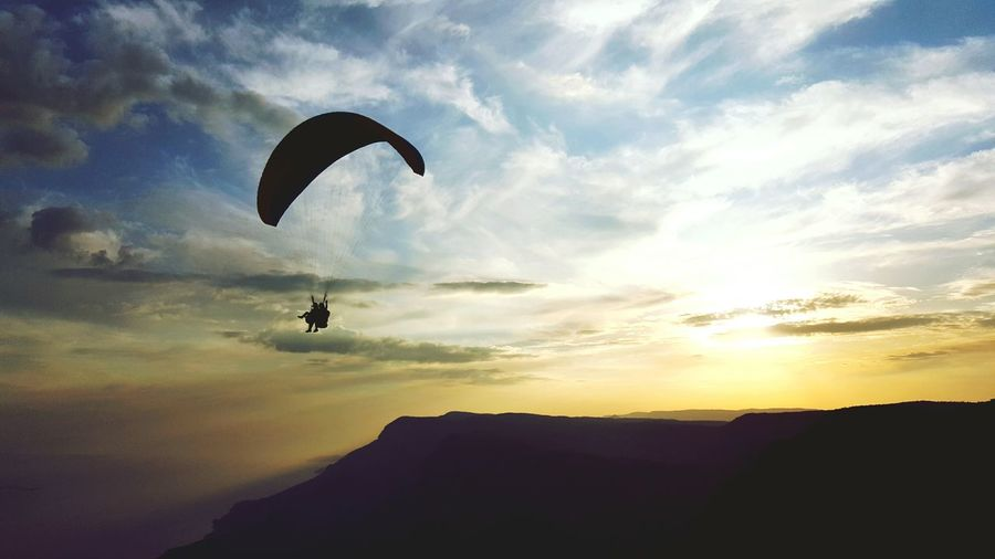 Low angle view of people paragliding over silhouette mountain during sunset
