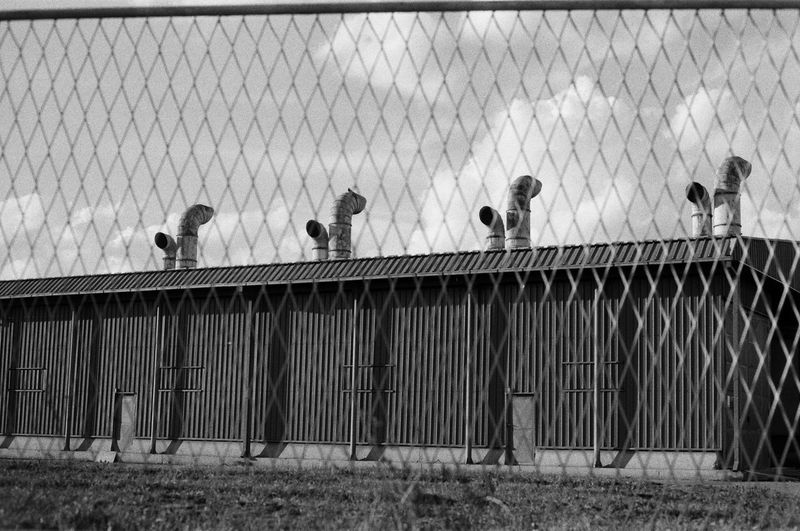 industrial district Focus On Foreground Outdoors 35mm Film Analog Film Photography Ilford Industrial EyeEm Selects EyeEm Best Shots EyeEmNewHere Prison Bird Architecture Building Exterior Sky Built Structure Chainlink Fence Terrace Chainlink Security Locked Fence Safety Protection Lock