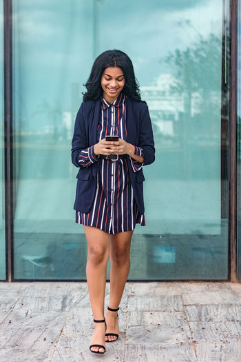 Full length of a young woman using phone