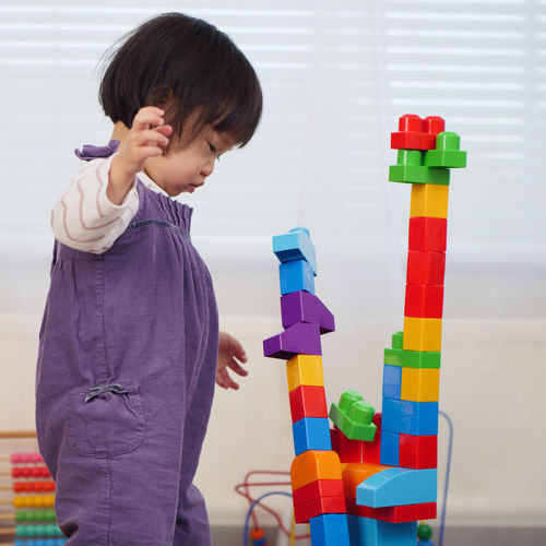 Asian Baby Girl Babygirl Built Structure Casual Clothing Childhood Day Focus On Foreground Holding Indoors  Learning Leisure Activity Lifestyles Multi Colored One Person People Playing Preschool Real People Sand Pail And Shovel Stack Standing Toy Toy Block