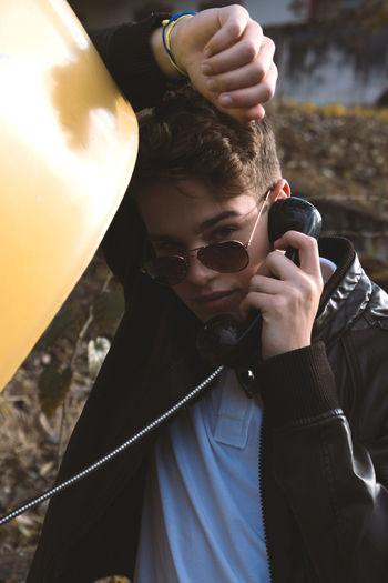 Portrait Of Teenage Boy Wearing Sunglasses Using Telephone