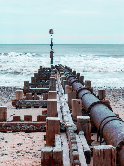 Scenic view of sea against sky with groyne and pipe