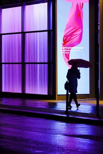 Side view of woman walking on glass window