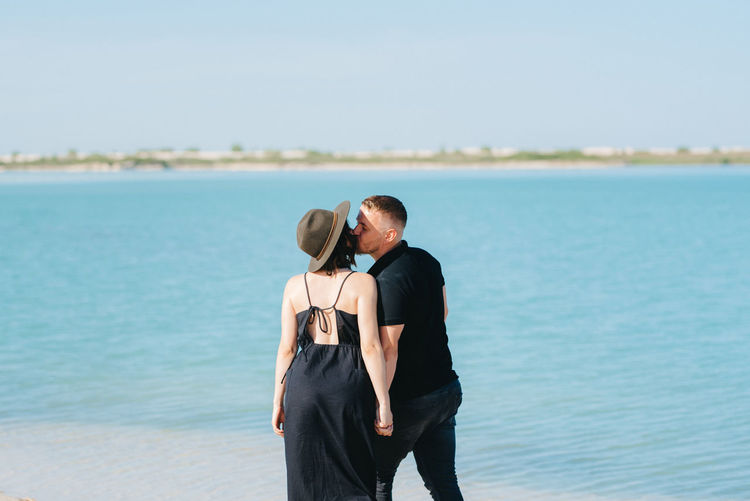 Rear view of couple standing in sea against sky