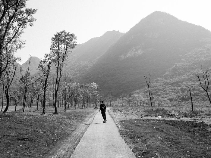 Man walking on road by mountains