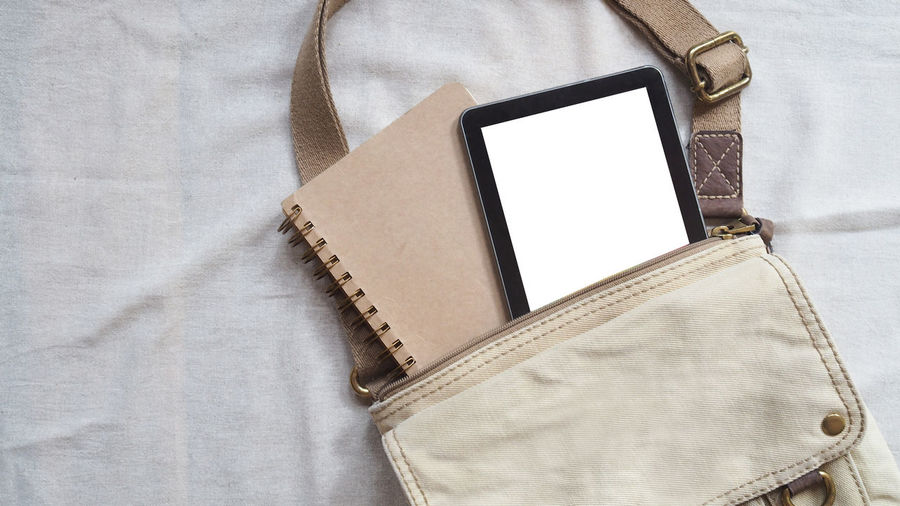 Place of work, blank digital tablet, old book with pencil and vintage leather bag on white color background, vintage color tone process for business and education concepts Communication Technology Connection Wireless Technology Close-up Indoors  No People Still Life Pocket  Portable Information Device Bag Mobile Phone Smart Phone High Angle View Personal Accessory Portability Paper Table Textile Purse Leather Jeans Open Book  Workplace