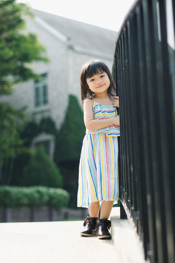 Full length portrait of girl standing by railings