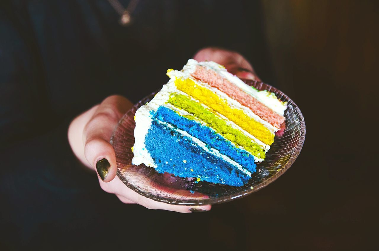Midsection Of Woman Holding Rainbow Cake In Plate